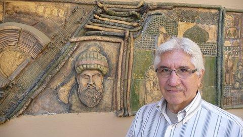 Mehmet Abu devant son cabinet et la fresque représentant Ibn Sina, plus connu sous le nom d'Avicenne.